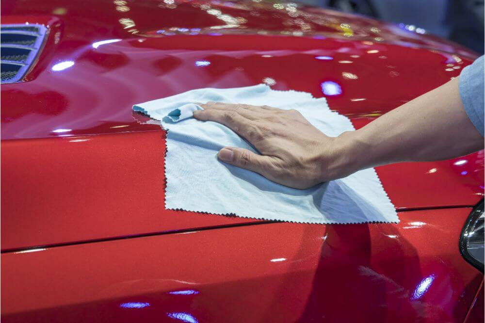 Waxing a car with cloth after applying wax. Car red paint work is shining
